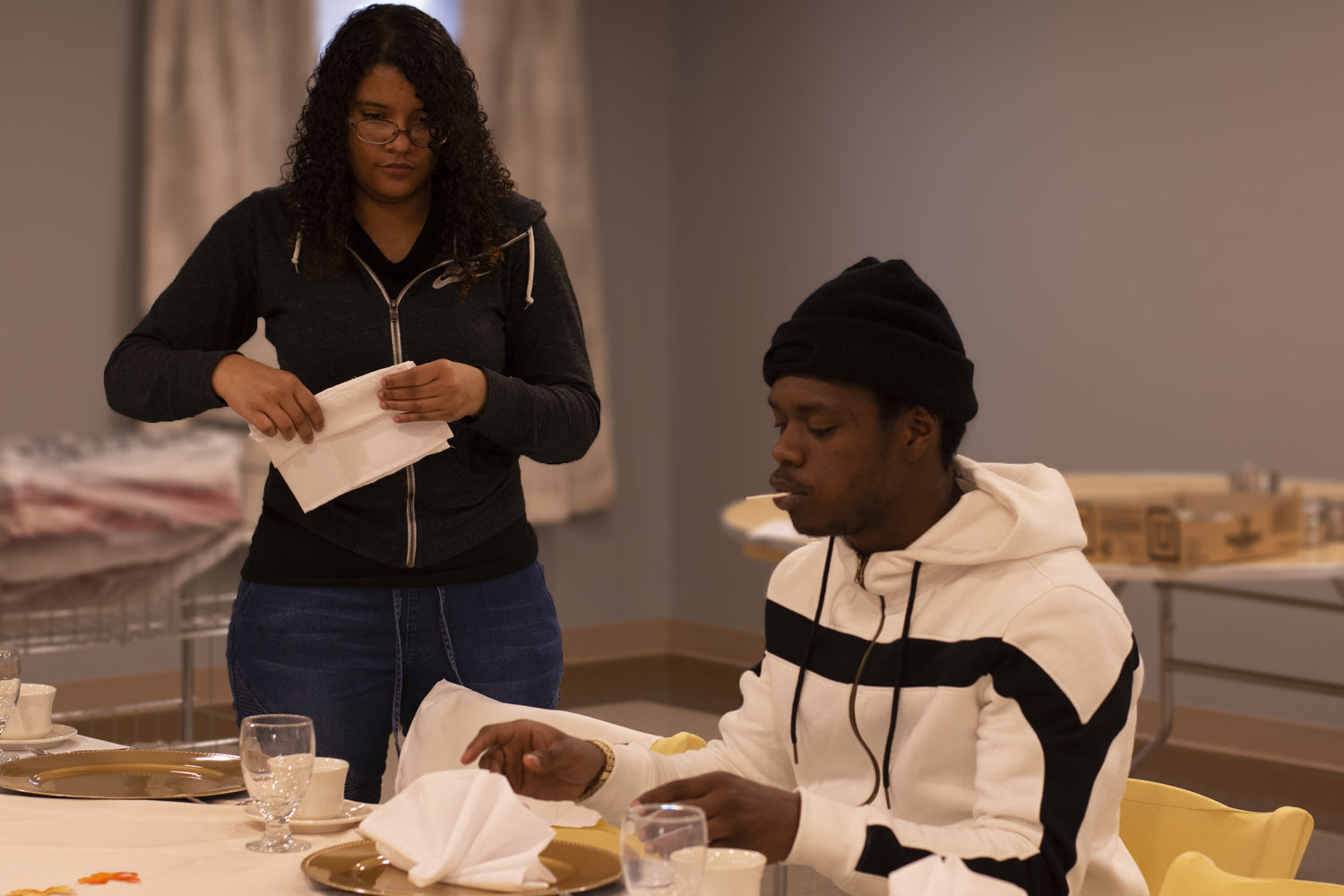A female and male student practice folding napkins for a banquet display.