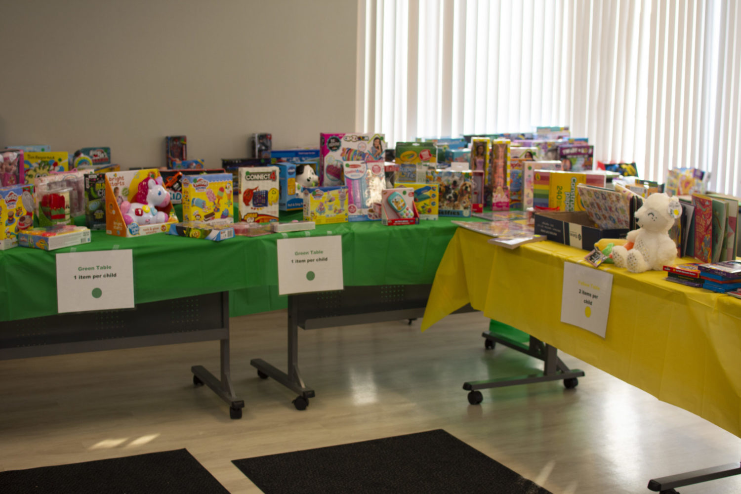 Two tables are covered with toys for the Adopt a Family store.