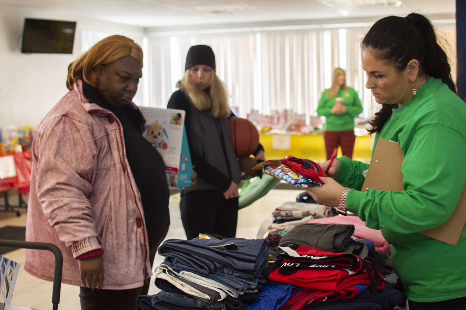 An Adopt a Family volunteer helps a woman shop for clothes.