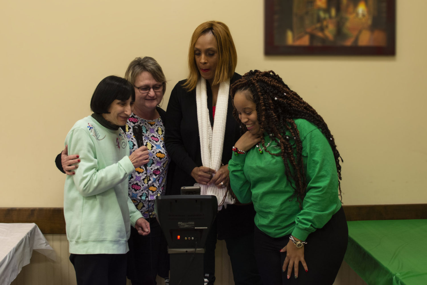 A group of four women sing Christmas carols on a karaoke machine