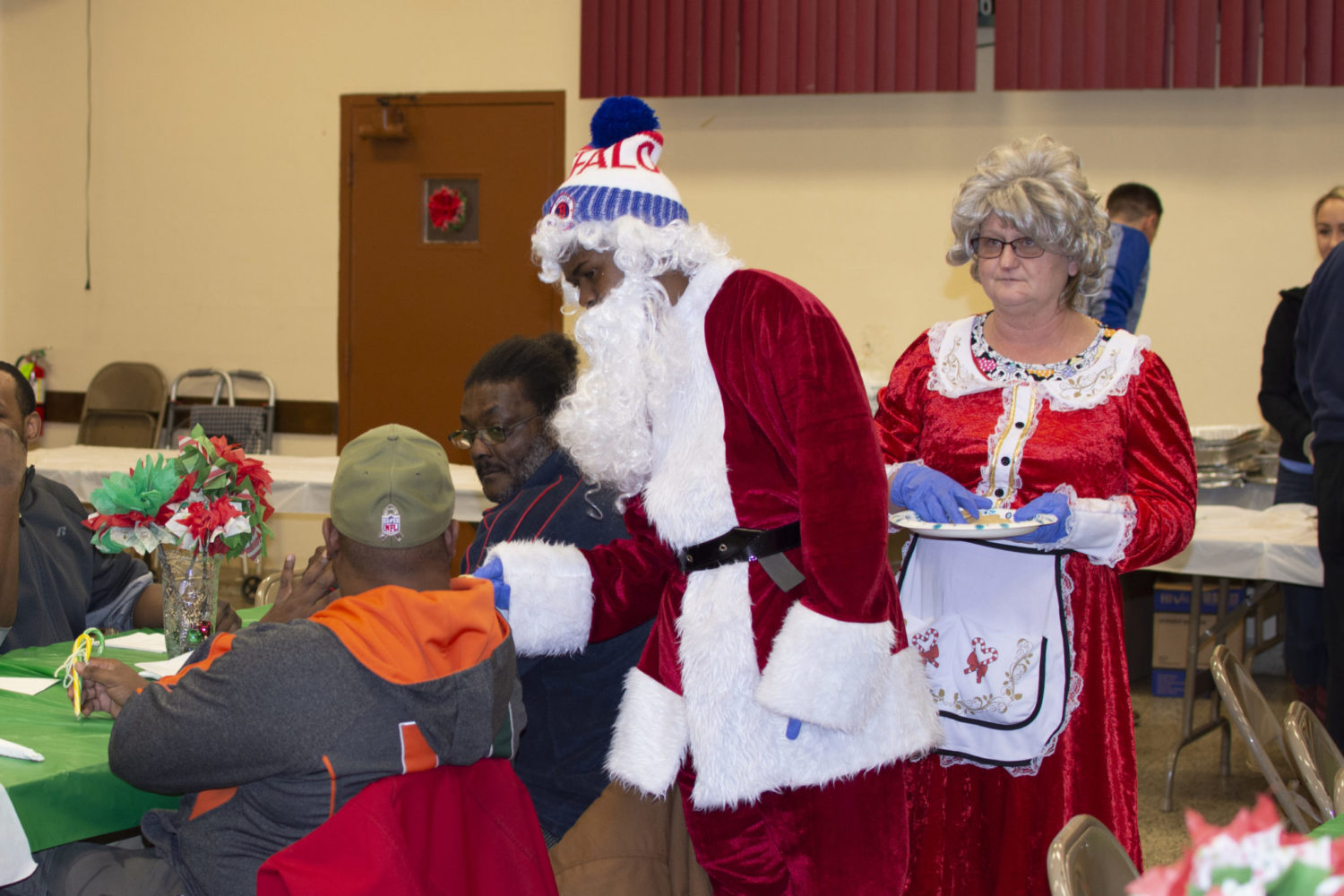 Santa and Mrs. Claus greet people at tables