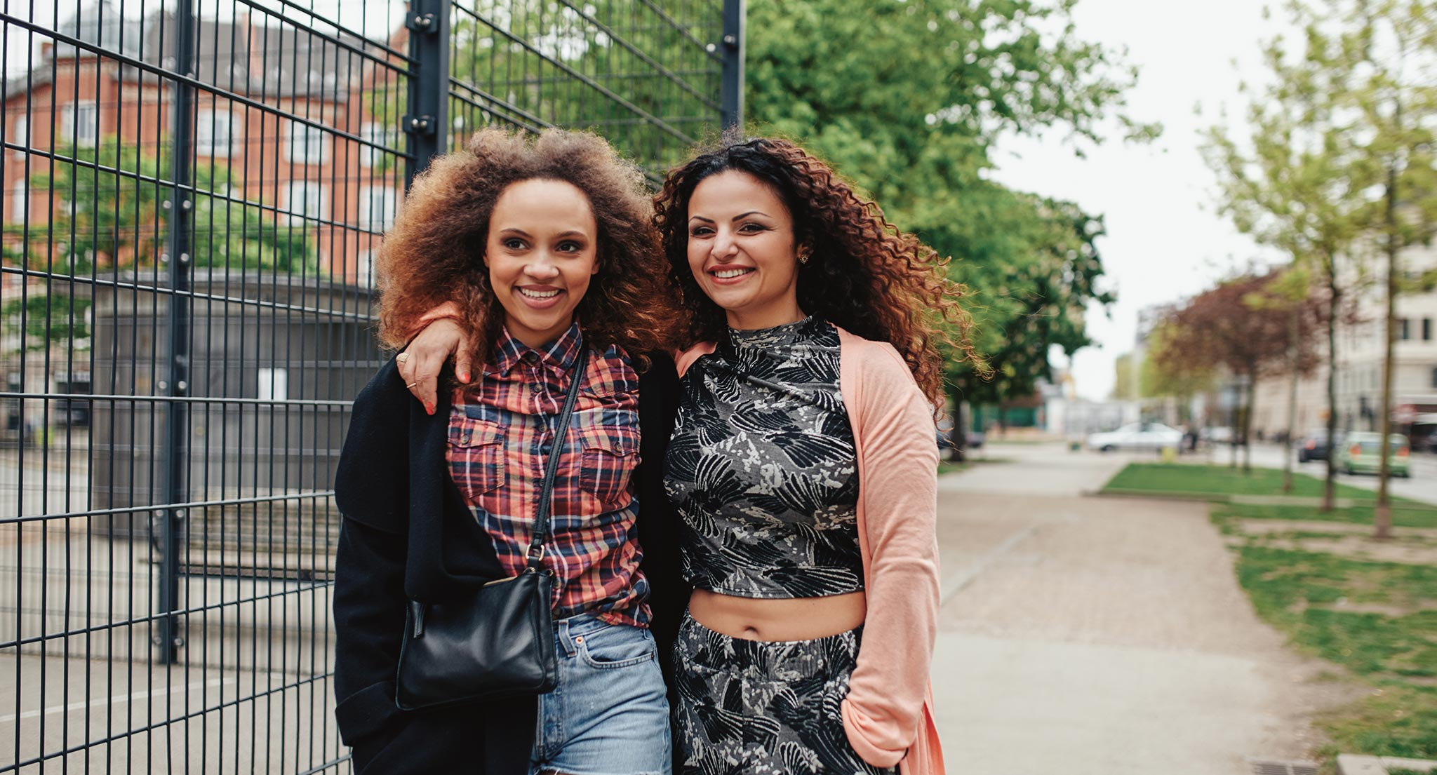 Two women smiling. One women has her arm around the other ones shoulders.