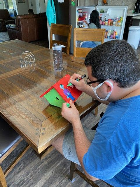 A young man uses paint markers to decorate a birdhouse