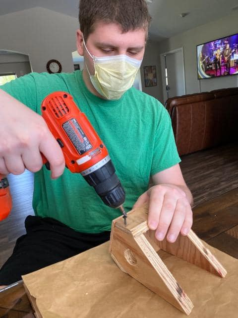 A young man uses a power drill to make a birdhouse