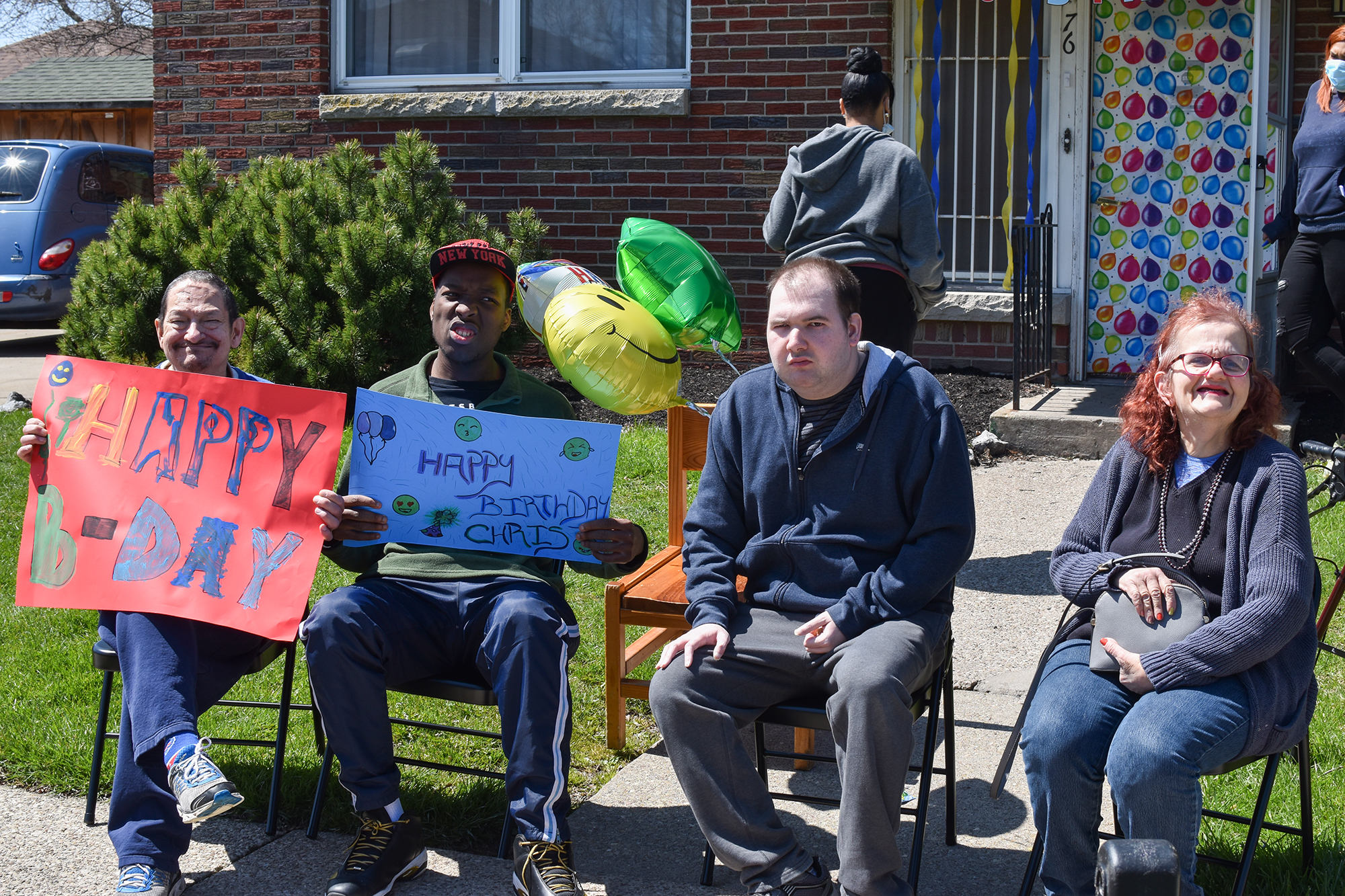 A group of residents sit outside with birthday signs