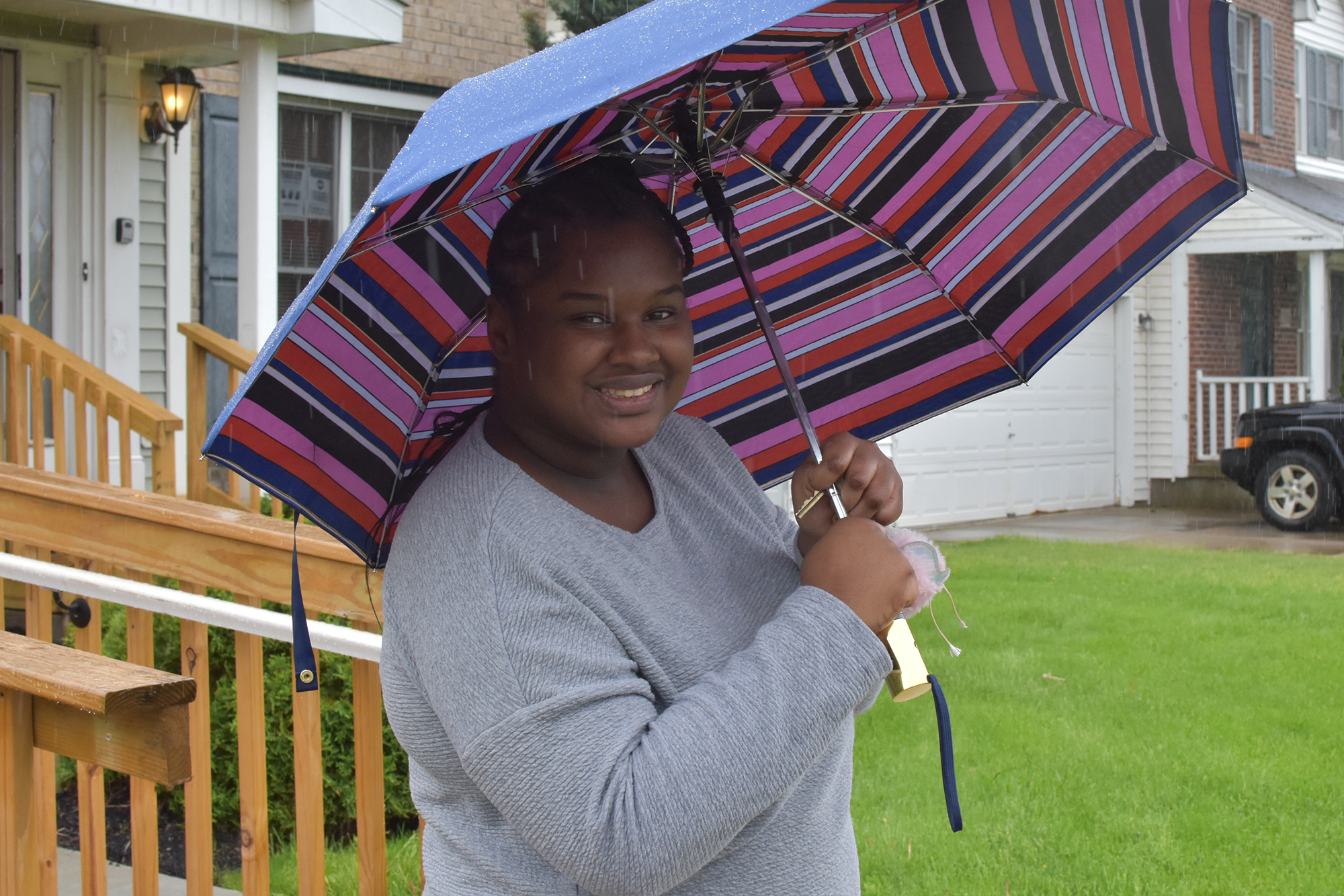 A young woman smiles as she holds an umbrella over her head