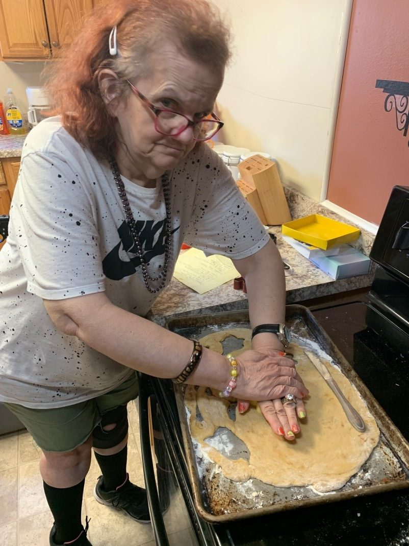 A woman cuts out shapes in dough