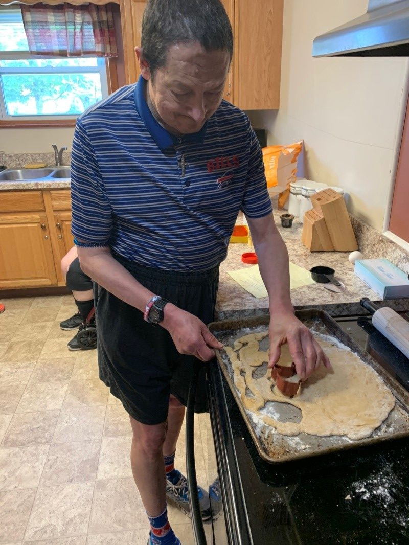 A man cuts out shapes in dough on a cookie sheet