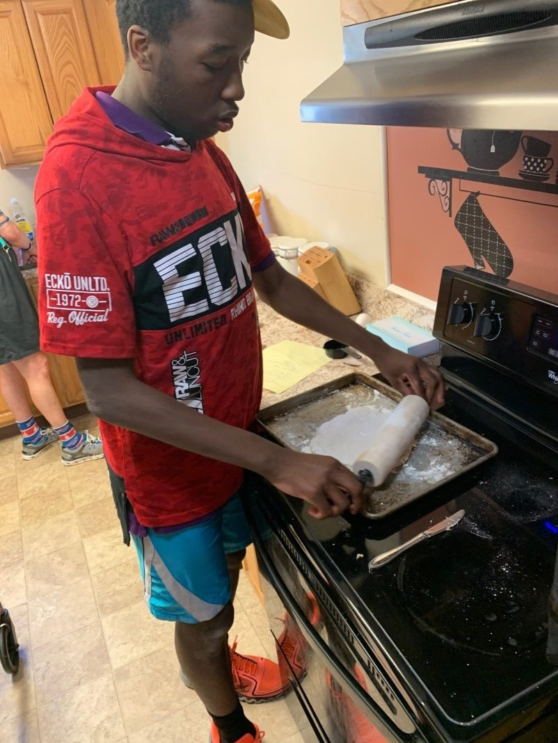 A man rolls out dough on a cookie sheet