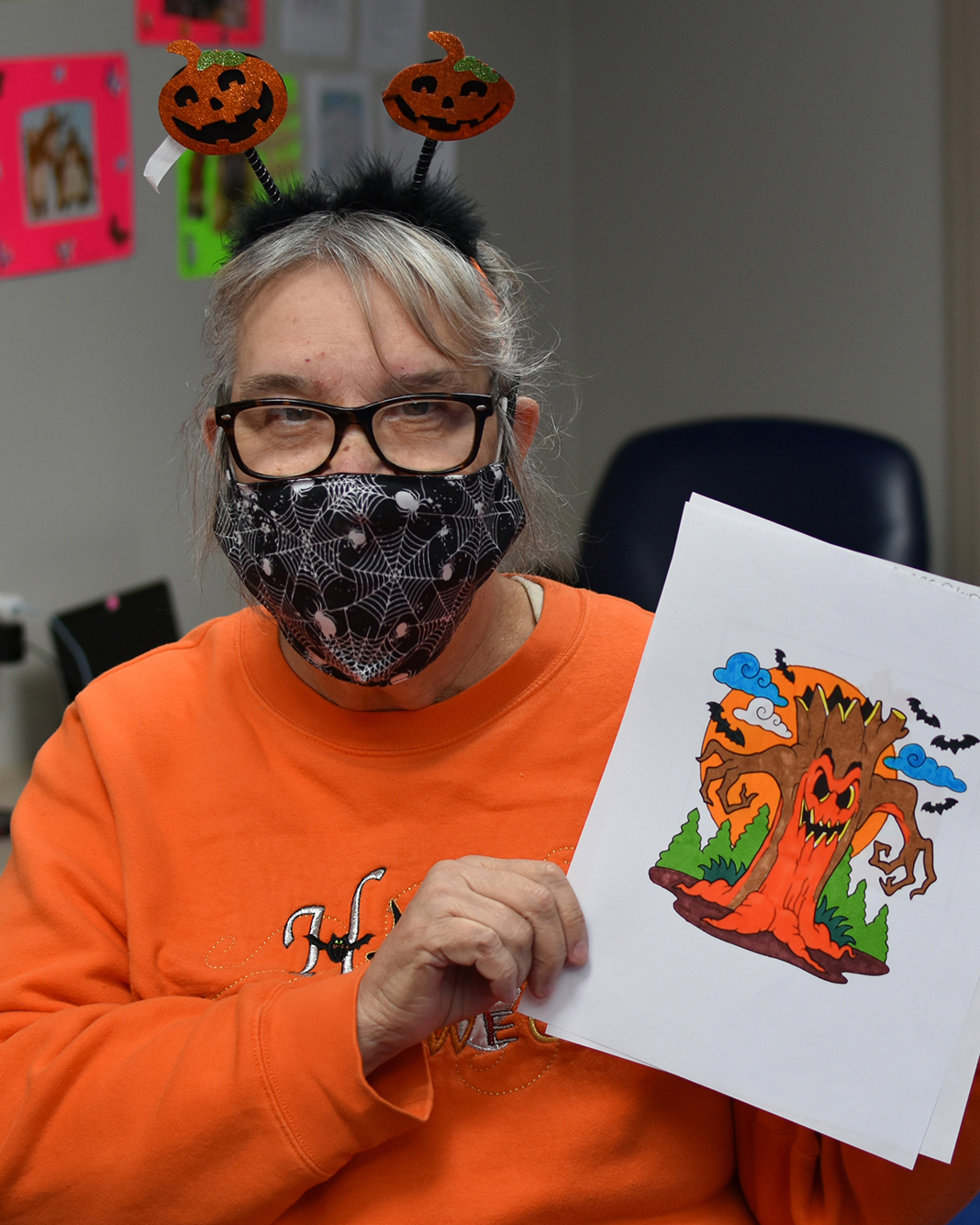 A woman we support holds up a Halloween picture that she colored
