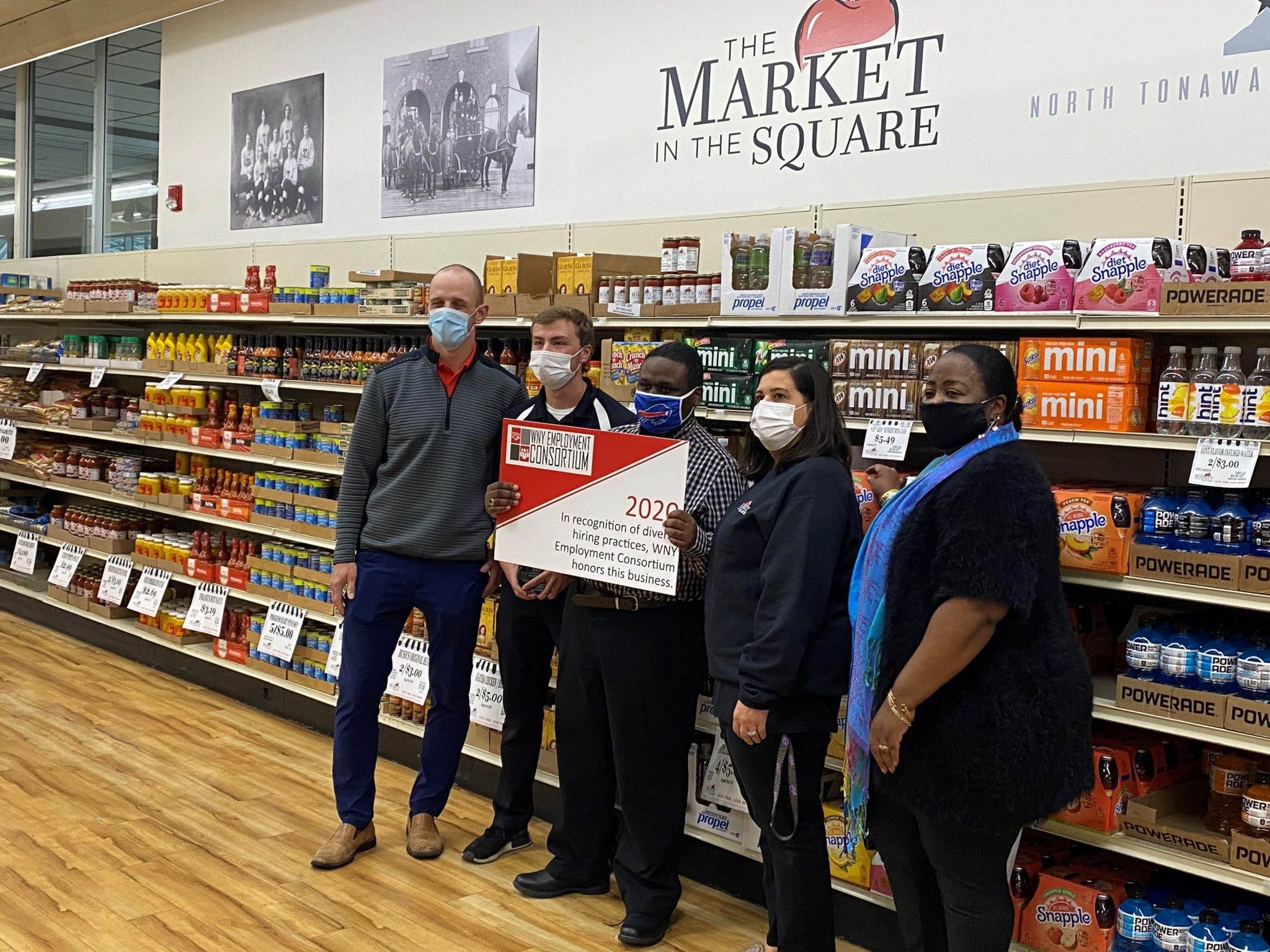 Market In the Square staff pose with Marcus and their Exemplary Employer sign.