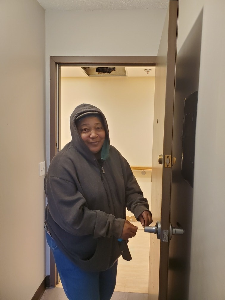 A picture of a person we support opening the door to their new home