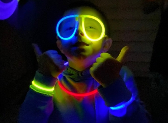 A young man wearing glow sticks gives the thumbs up
