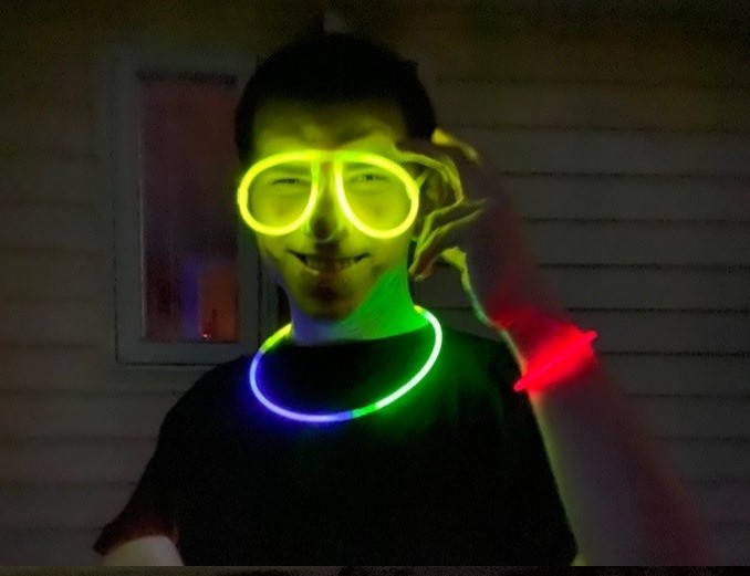 A young man we support wears glow stick glasses