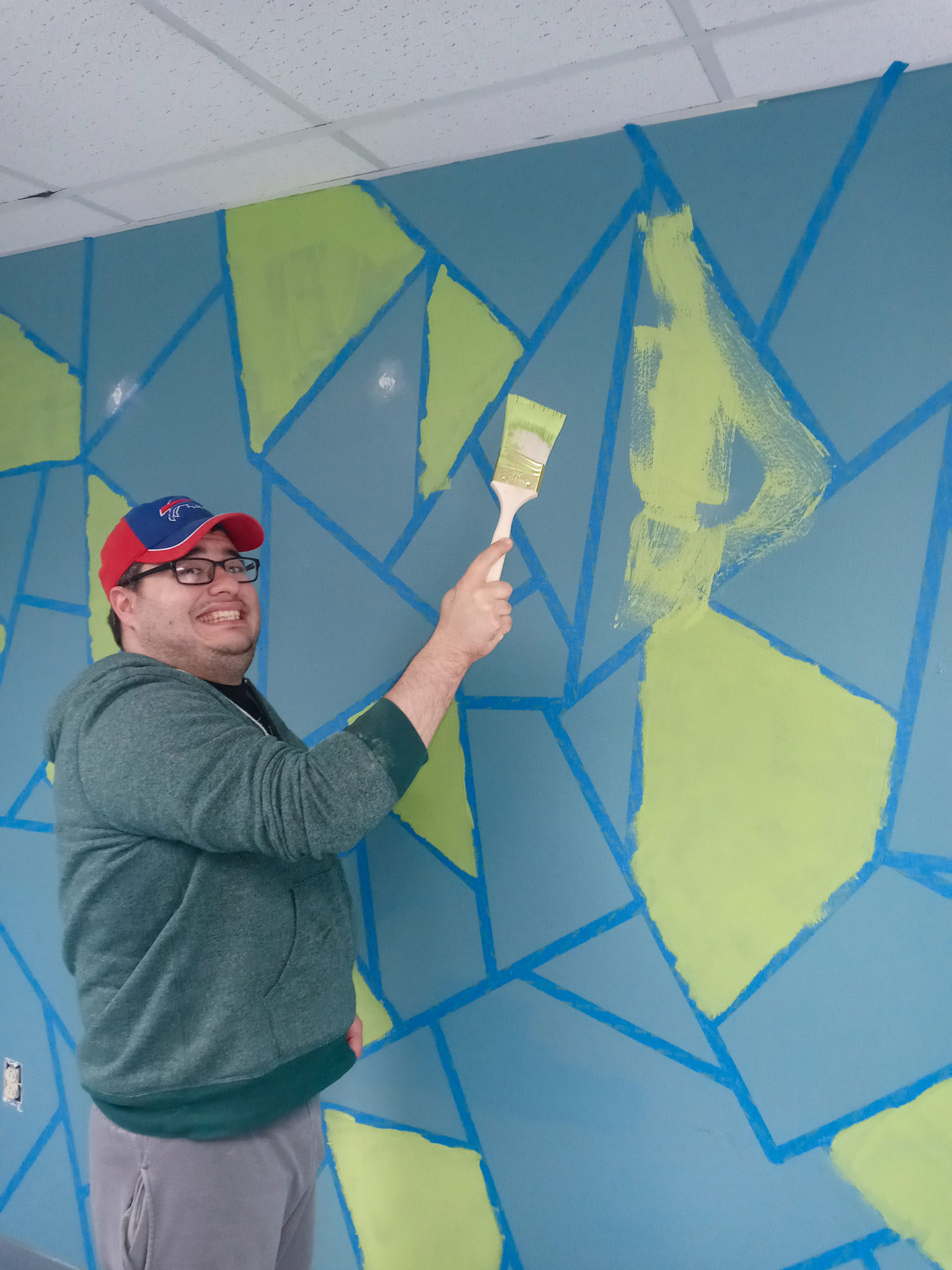 A young man we support paints part of the wall design