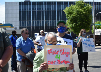 A man holds a sign asking for fair wages for DSPs
