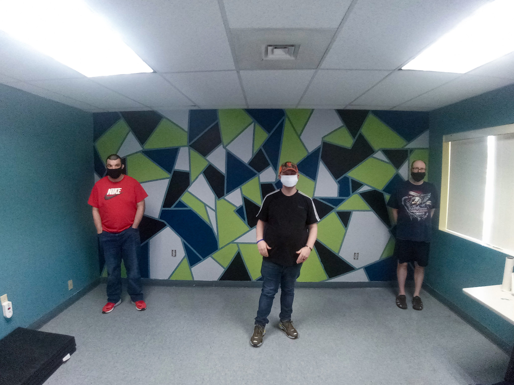 Three of the guys who helped paint the wall pose with the finished product