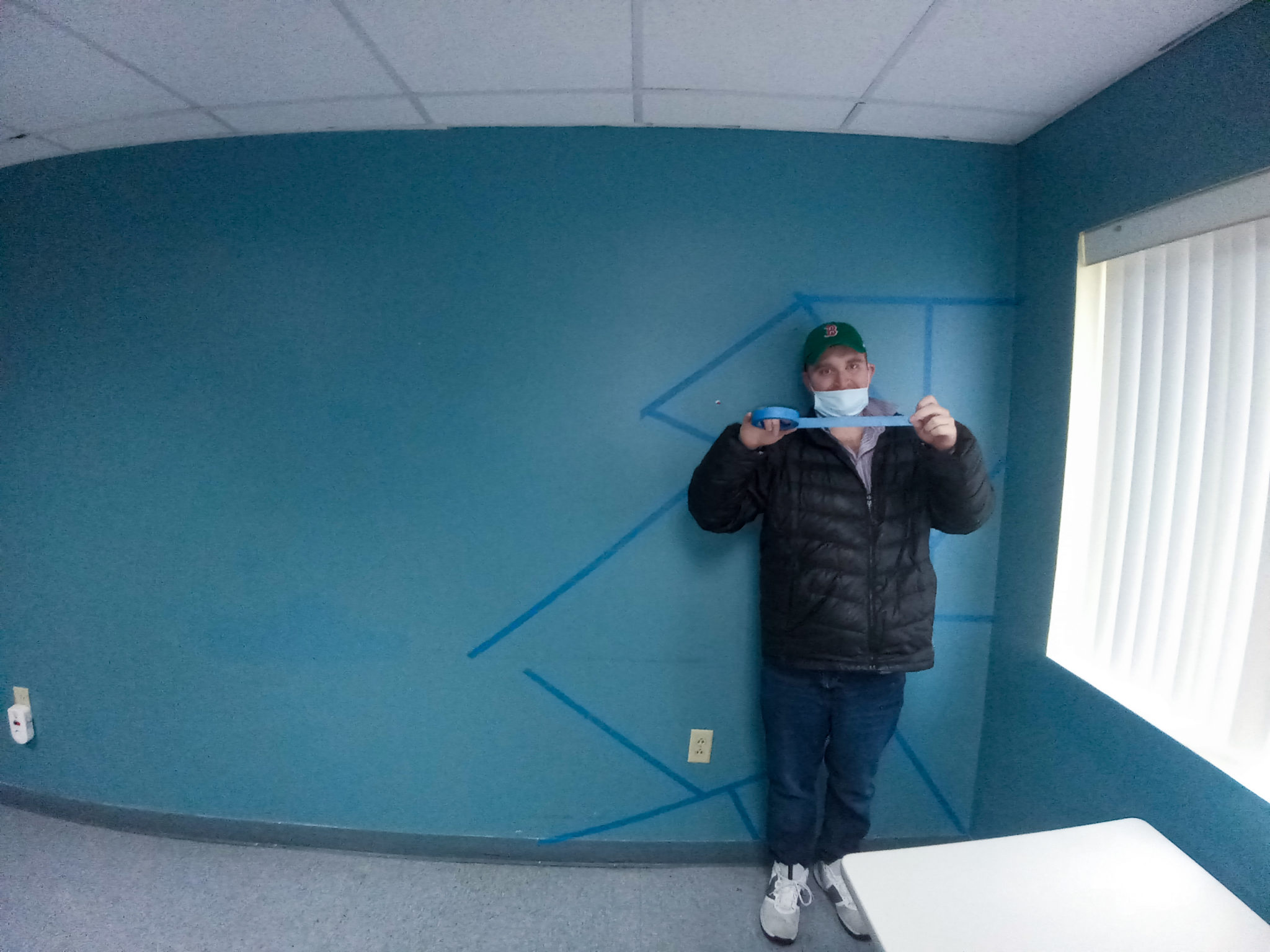 A man we support begins taping the abstract designs on the wall