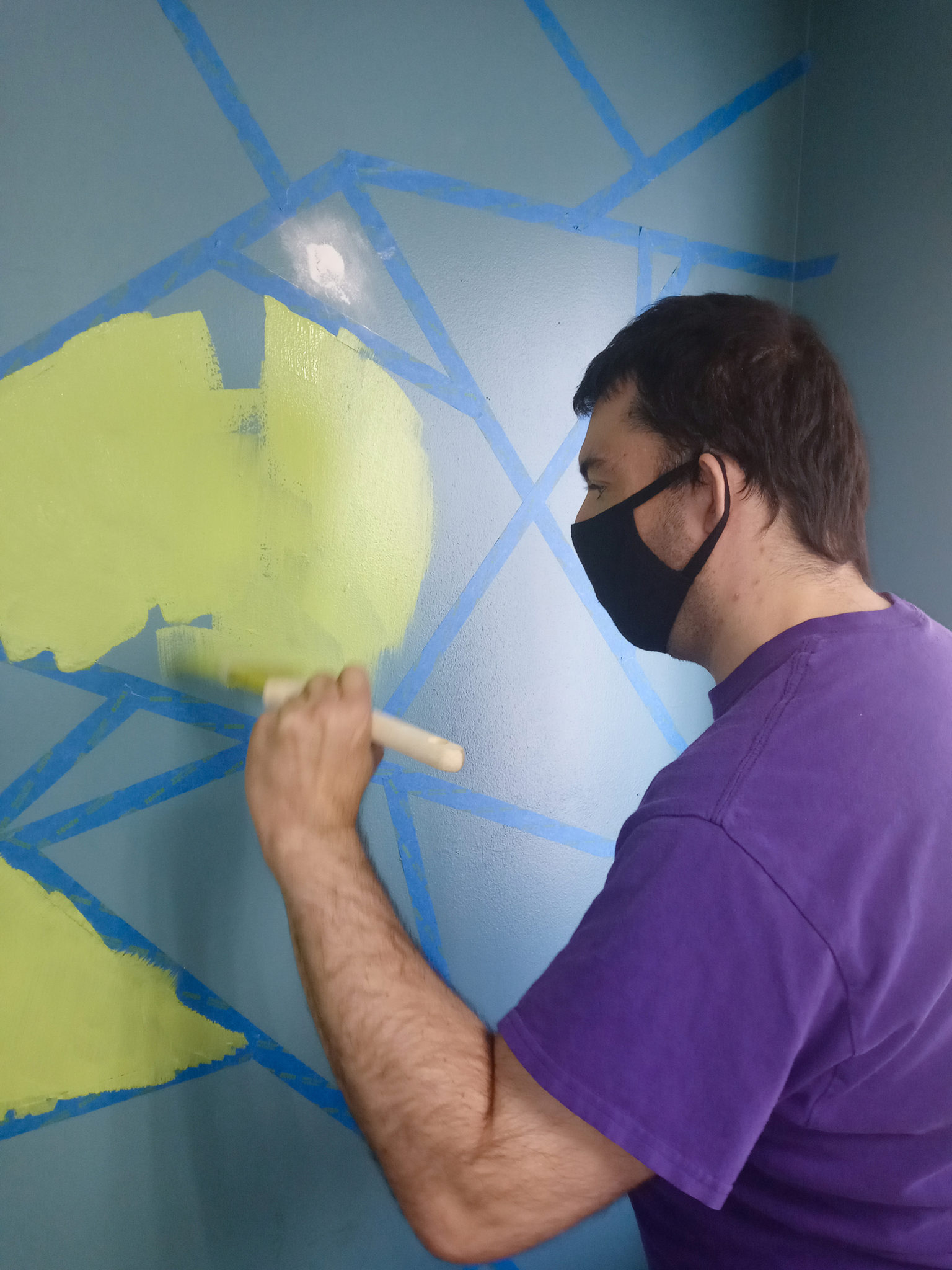 A young man we support concentrates on painting part of the wall design