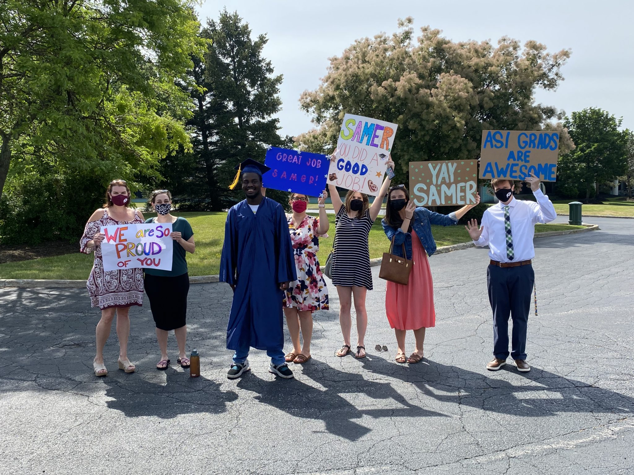 Samer poses with his teachers and Community Services staff as they hold up signs of support and congratulations.